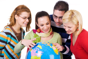 Group of students holding a world globe
